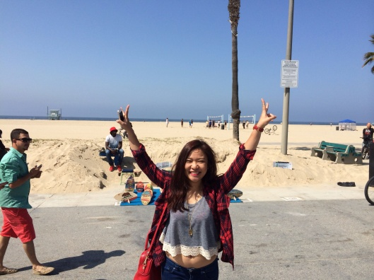 Do Huong Tra My is off her feet with her arms in the air on Venice Beach!