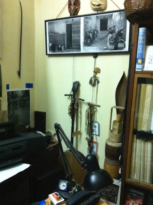 Old instruments line the wall in Tan's Hanoi apartment.
