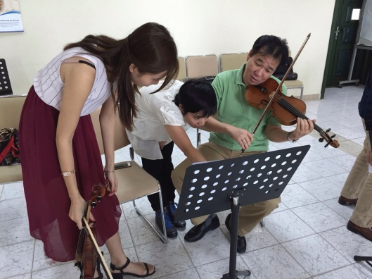 Kimngoc Tran discusses a detail with violinists Khanh Linh and Pham Truong Son.