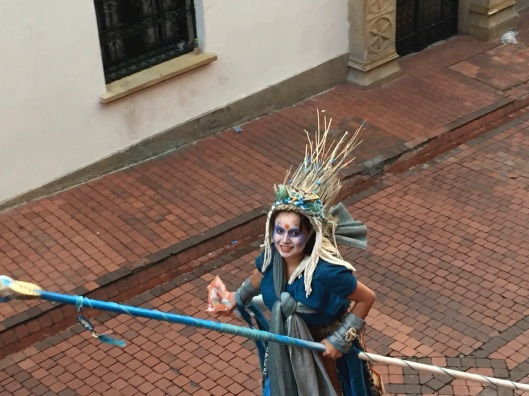 A kind hearted stilt lady in blue greets me from the street.