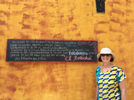 Jan against the colorful wall and sign of El Boliche in Cartagena.