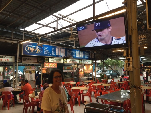 Jan in the Batu Ferringhi food court, and yes that's MLB baseball on behind her