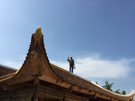 A worker greets us from the pagoda roof of Chua Linh Am.