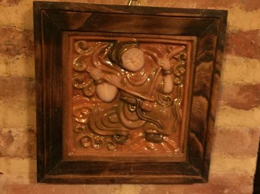 A glazed ceramic wall hanging.