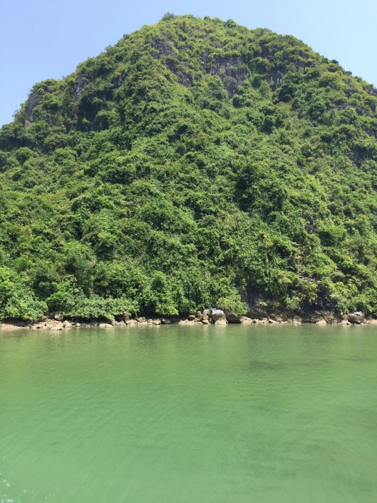 The green water of noon surrounds. Cat Ba Island.
