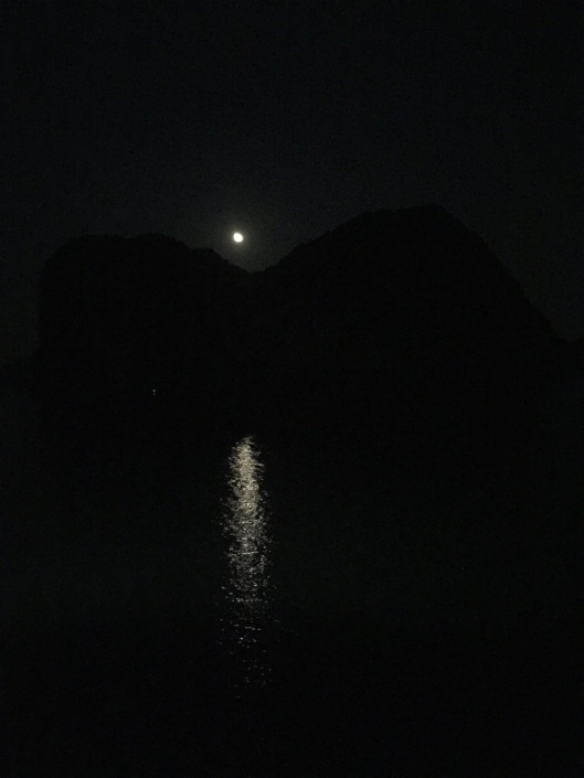 Moonrise over a limestone karst cliff in Ha Long Bay.