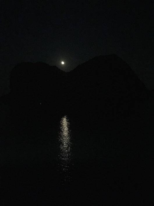 Moonrise over a limestone karst cliff in Ha Long Bay.